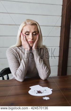 Sad Elderly Woman With Dementia Sitting Near Blurred Jigsaw On Table