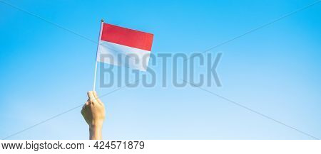 Hand Holding Indonesia Flag On Blue Sky Background. Indonesia Independence Day, National Holiday Day
