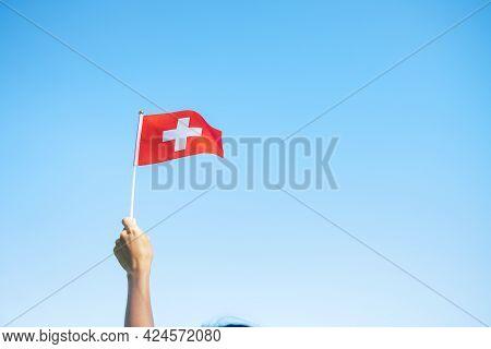 Hand Holding Switzerland Flag On Blue Sky Background. Switzerland National Day And Happy Celebration