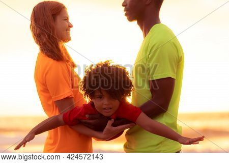 Multiethnic Family Having Fun On Summer Vacation. Father, Mother And Daughter Against Sunset Backgro