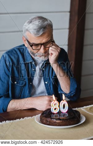 Lonely Man Looking At Blurred Birthday Cake With Candles In Shape Of Eighty Numbers