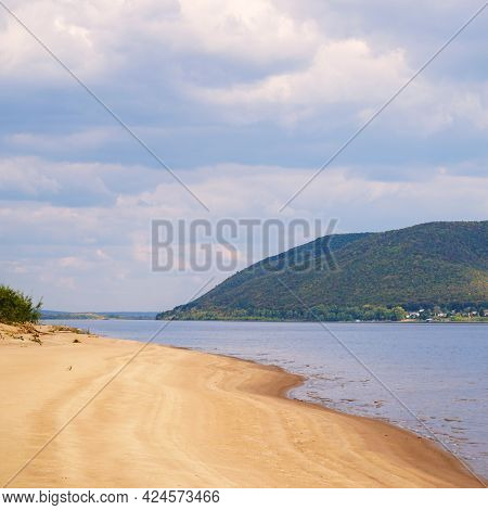 The Sandy Shore Of The Big Volga River Against The Background Of A Cloudy Sky. On The Opposite Bank