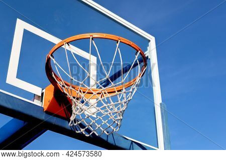 Street basketball hoop on a sunny day with blue sky in the background.