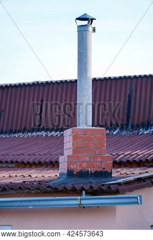 Pipe Chimney On The Roof Against The Light Sky