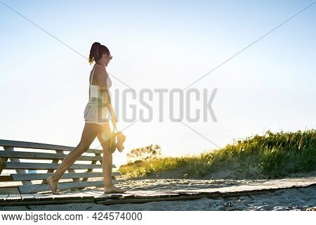 Summer Evening Walk On The Beach Boardwalk At Dawn. Lonely Sad Young Woman In Melancholy Or Solitude
