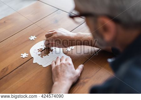 Blurred Man With Dementia Folding Jigsaw On Table At Home