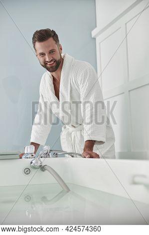 Smiling Man In Bathrobe Looks At Modern Hydro Massage Tub Full Of Hot Water In Salon
