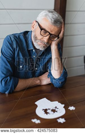 Sad Senior Man With Dementia Looking At Jigsaw On Table
