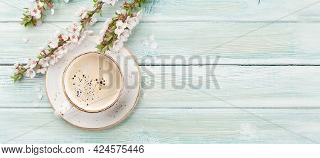 Morning espresso coffee cup on wooden table and cherry blossom. Top view flat lay with copy space