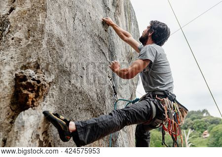 Young Man Climbing And Overcoming A Difficult Obstacle In The Mountain. Risk Sport And Mountain.