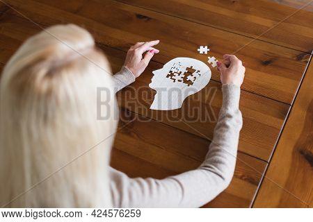 Overhead View Of Senior Woman With Dementia Folding Jigsaw