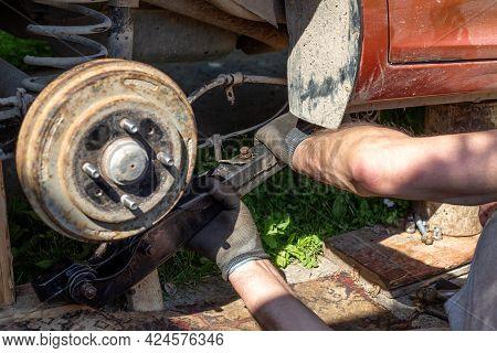 Car Lever Repair. The Technician Puts The Rear Arm Into The Car.