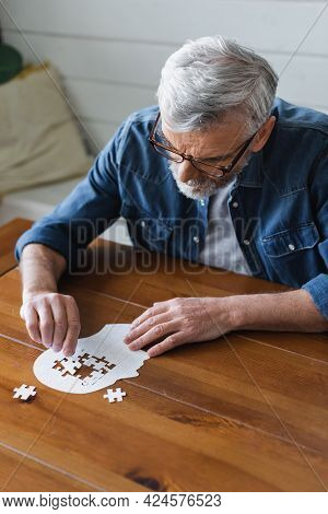 Senior Man With Dementia Holding Puzzle On Table