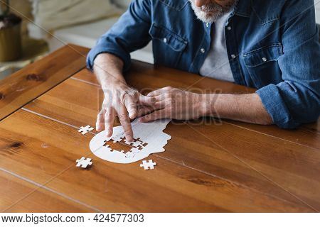 Cropped View Of Elderly Man With Alzheimer Folding Puzzle