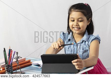A Pretty Indian Girl Child Attending Online Class With Tablet On White Background