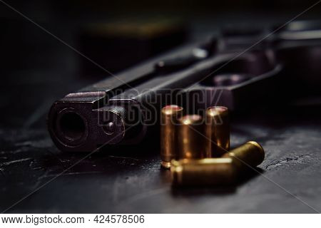 Firearms On Concrete Background. Close-up Of Gunpoint And Bullets On Table. Weapons And Ammunition.