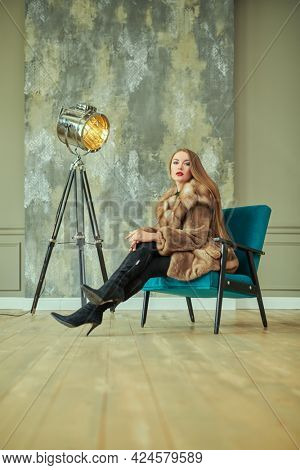 Beautiful glamorous woman in an expensive mink and sable fur coat poses in luxury apartments. Fur coat fashion. Full length portrait.
