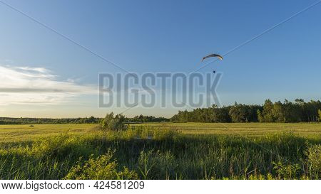 A Powered Paraglider Flying Over The Idyllic Meadow On A Sunny Day. Summer Landscape With Moto Parag