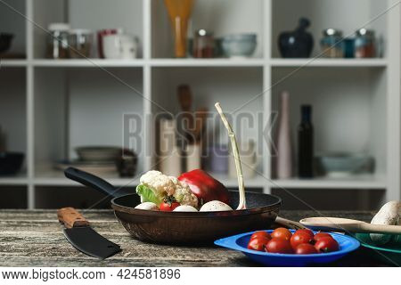 Cooking Pan And Vegetarian Cuisine Ingredients At Kitchen Counter. Utensils On Blur Kitchen Room Bac