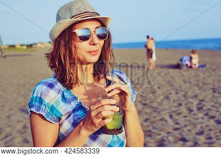 Traveler girl relaxing on tropical beach in vacation. Young girl traveler relaxing in vacation. Traveler relaxing on tropical beach in vacation. Girl in vacation relaxes on beach in summer day. Traveler. Summer. Vacations.