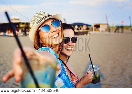 Girl friends drinking cocktail on beach in vacation. Young girl friends relaxing in vacation. Friends relaxing on tropical beach in vacation. Girls in vacation relaxes on beach in summer day. Traveler. Summer. Vacations.