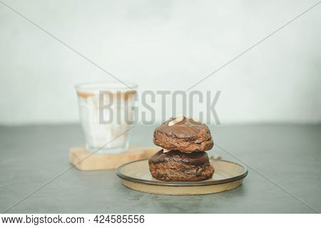 Chocolate Scones With Nut On Top And A Cup Of Hot Latte On Table