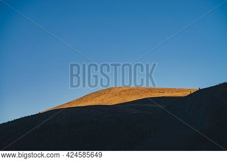 Autumn Landscape With Dark Silhouettes Of Mountains And Vivid Beautiful Orange Mountain Top In Golde