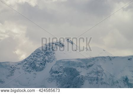 Atmospheric Highland Landscape With High Snowy Mountain Wall Under Cloudy Sky. Dramatic Scenery With