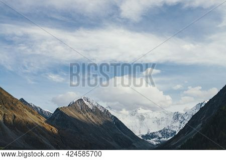 Awesome Alpine Landscape With Snow-covered Mountain Tops And Rocks In Golden Sunshine Under Cloudy B