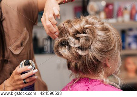 The Girl-hairdresser Makes The Client A Hairstyle For A Celebration. The Hairdresser Fixes Everythin
