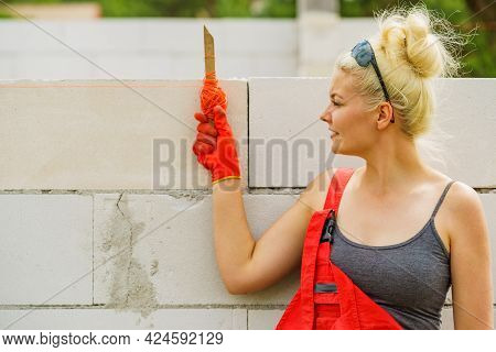 Woman Builder Using String As Level In Wall Construction. Bricklayer, New House In Progress.