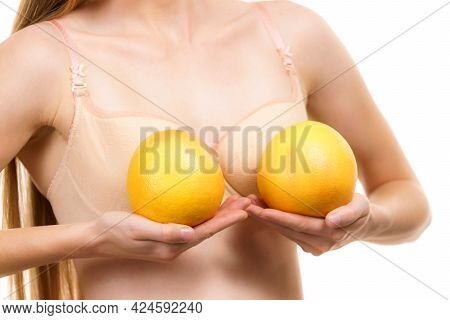 Slim Young Woman Small Boobs Wearing Bra Holding Big Orange Fruits. Breast Enlargement Size Correcti
