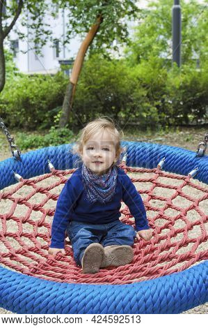 Cute Little Child Having Fun On A Colorful Swing Outdoor In The Park. Beautiful Spring Day In Childr