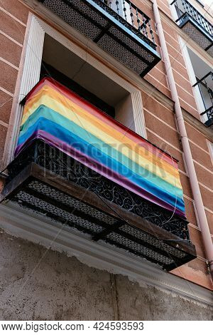 Low Angle View Of Balcony With Rainbow Flag In Chueca Neighbourhood In Madrid