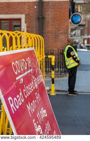 London, Uk - May 30, 2021: A Covid-19 Sign Saying Road Closure Ahead With A Workman In A Hi-vis Jack