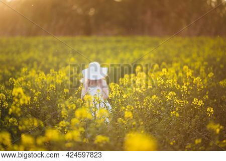 A Blurred Little Girl In White Dress Running Through The Rape Field At Sunset. Intentional Sun Glare