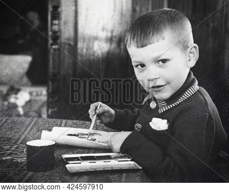 Retro Portrait Of Soviet Boy Drawing With Paints On Paper. Vintage Black And White Paper Photo. Earl