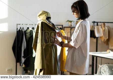Concentrated Young Dressmaker, Designer Work On Coat On Mannequin In Modern Workshop Studio. Busines