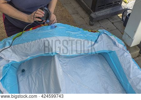 Close Up View Of Woman Inflating Inflatable Pool For Children Using An Electric Pump. Sweden.