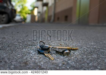 The Lost Bunch Of Keys Lies On The Asphalt Road Near The Entrance Of The House, Near The Door Of A M