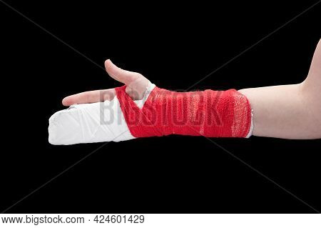 Broken Hand With White Gypsum And Red Bandage, Isolated On Black Background.