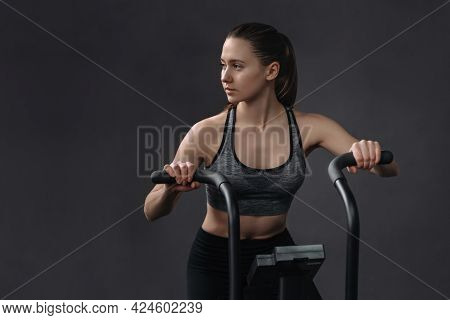 Attractive Young Woman In Sportswear Using Exercise Bike For Cardio Workout At Fitness Gym. Fit Pret