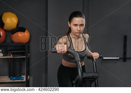 Portrait Of Attractive Young Woman Training On Air Bike In Gym. Female Athlete Doing Cardio Exercise