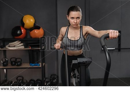 Portrait Of Female Sport Athlete Using Air Bike For Cardio Workout At Gym. Fit Young Brunette Woman