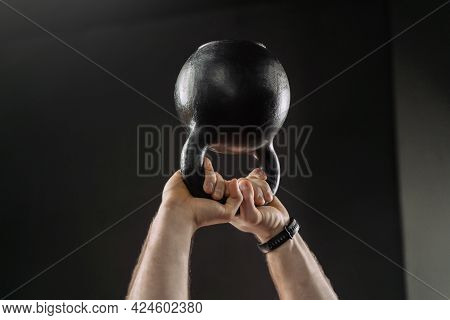 Close Up Of Muscular Man\'s Hands Holding Heavy Kettlebell Overhead. Hands Holding Heavy Kettle Bell
