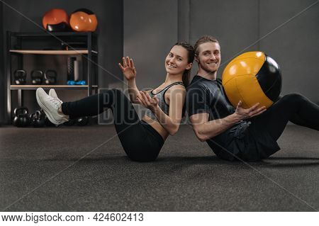 Happy Fitness Couple Training Together At Dark Gym With Professional Sport Equipment On Background.