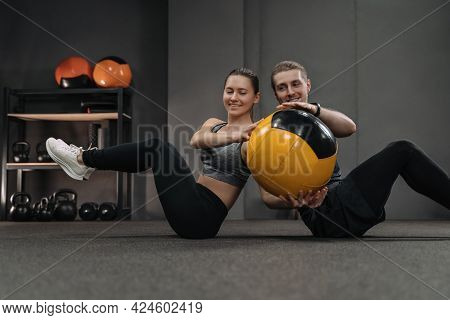 Healthy Young Couple Doing Abs Exercises With Medicine Ball At Dark Gym. Couple Sitting Back To Back