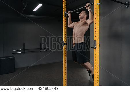 Strong Young Man Doing Pull Up Exercise On Horizontal Bar At Gym. Sports, Fitness, Gymnastics Workou