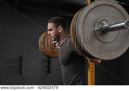 Portrait Of Male Bodybuilder Doing Back Squats In Gym. Muscular Handsome Young Man Getting Ready To