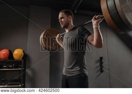 Handsome Young Sportsman Is Holding A Heavy Weight Barbell On The Shoulder Behind The Neck, Having W